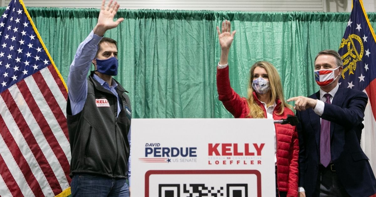 Sens. David Purdue and Kelly Loeffler wave to a crowd of supporters at a rally with Sen. Tom Cotton, left, at the Georgia National Fairgrounds and Agriculture Center on Nov. 19, 2020, in Perry, Georgia.