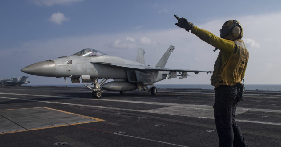 Aviation Boatswain's Mate 3rd Class Marnell Maglasang, from La Puente, California, directs an F/A-18E Super Hornet on the flight deck of the aircraft carrier USS Nimitz in the Arabian Sea on Nov. 27, 2020.