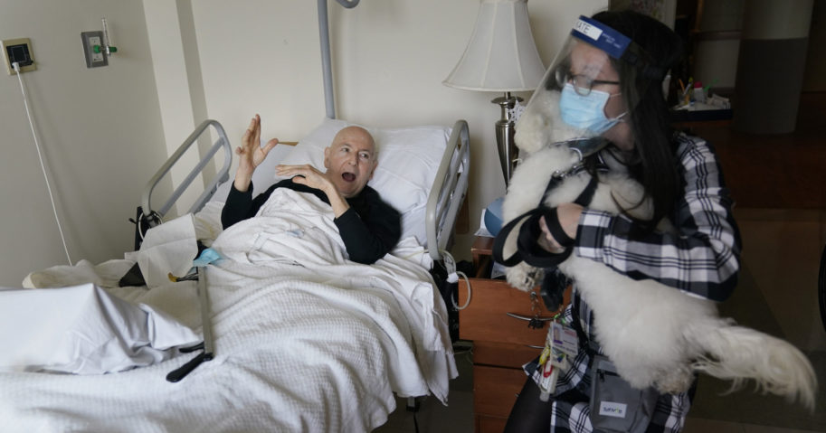 Jeff Philipson, 80, left, exclaims as therapeutic activities staff member Kate DelPizzo arrives for a visit with Zeus, a bichon frise, at The Hebrew Home at Riverdale in New York on Dec. 9, 2020.