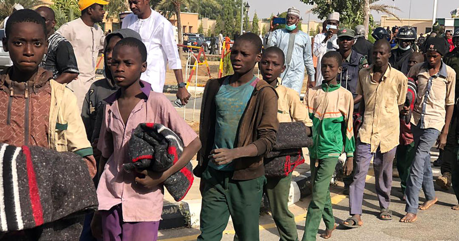 Schoolboys are escorted by the Nigerian military on Dec. 18, 2020, in Katsina state, Nigeria, following their release by their Boko Haram captors.