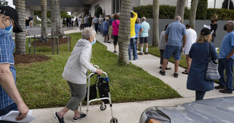 Seniors stand in line to make an appointment to receive the Moderna COVID-19 vaccine outside the King's Point clubhouse in Delray Beach, Florida, on Dec. 30, 2020.