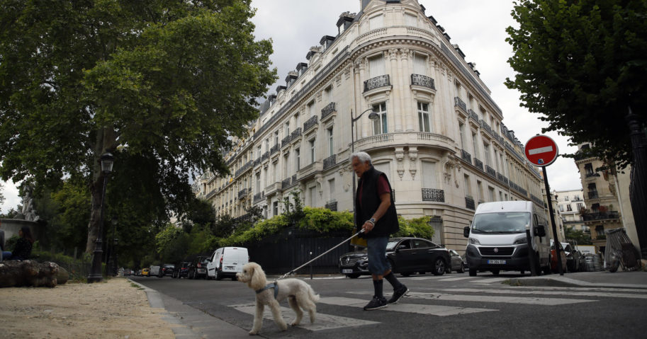 In this Aug.13, 2019, file photo, a man walks his dog next to an apartment building owned by Jeffrey Epstein in Paris.