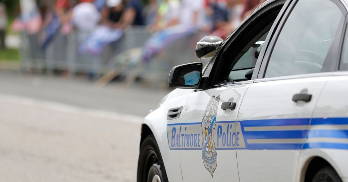A Baltimore police cruiser rolls by as people gather outside of Fort McHenry National Monument and Historic Shrine on May 25, 2020, in Baltimore, Maryland.