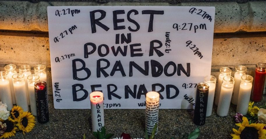 A sign is seen at a candlelight vigil for Brandon Bernard on Sunday in Los Angeles.