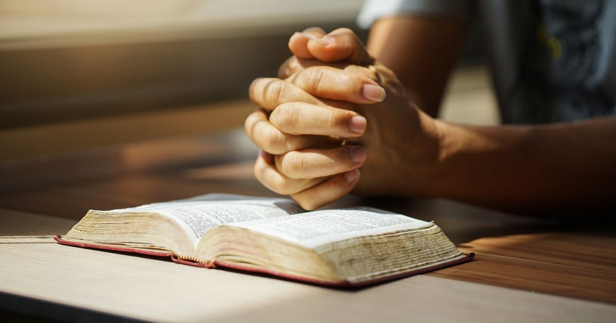 A person praying over a Bible is pictured in the stock image above.