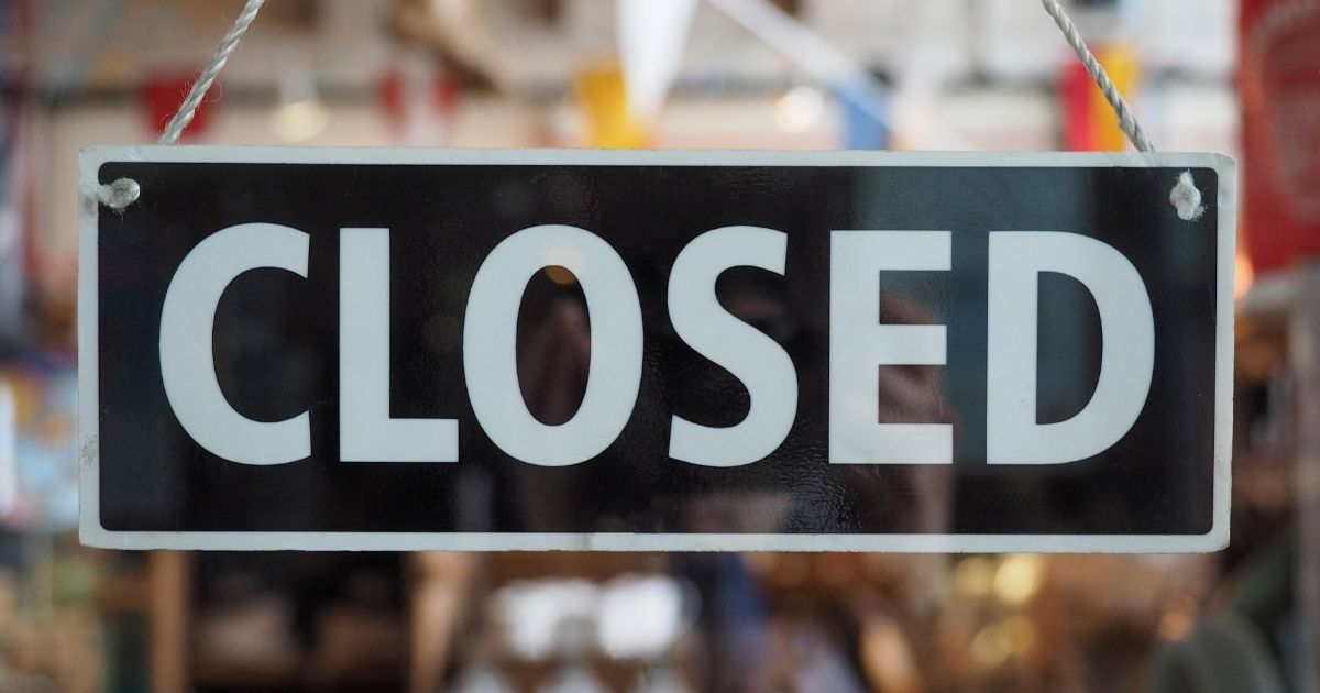 """A """"closed"""" sign on a business' door is pictured in the stock image above."""