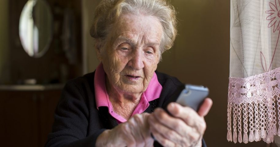 An elderly woman uses a smartphone.