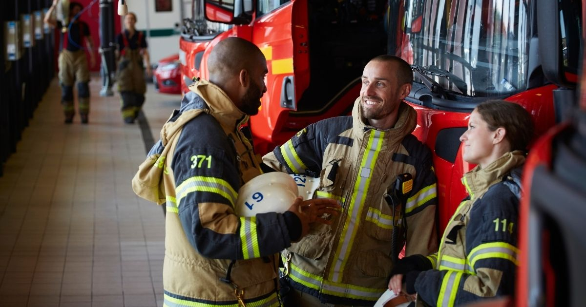 More than half of New York City's firefighters who participated in a union survey have said they have no plans to be vaccinated against COVID-19. The above stock image shows firefighters talking in uniform.