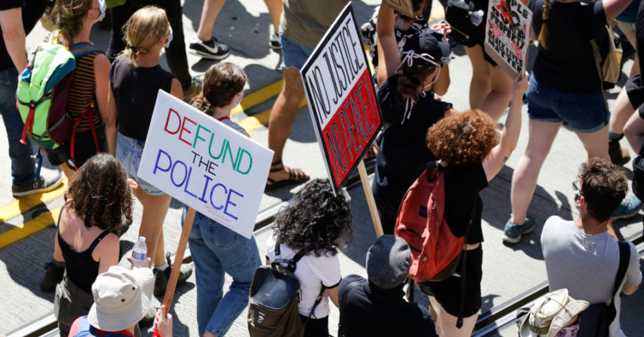 """People carry signs during a """"Defund the Police"""" march from King County Youth Jail to City Hall in Seattle, Washington on August 5, 2020."""