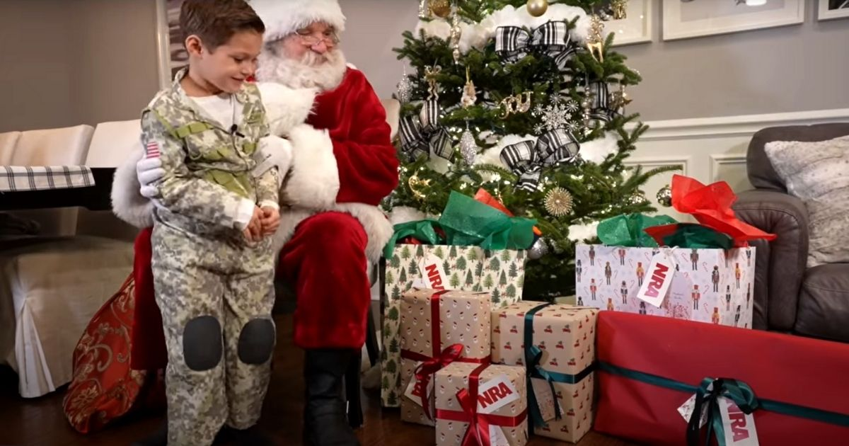 The NRA Santa Claus shows 4-year-old Michael DeCarlo the gifts he brought for the boy.