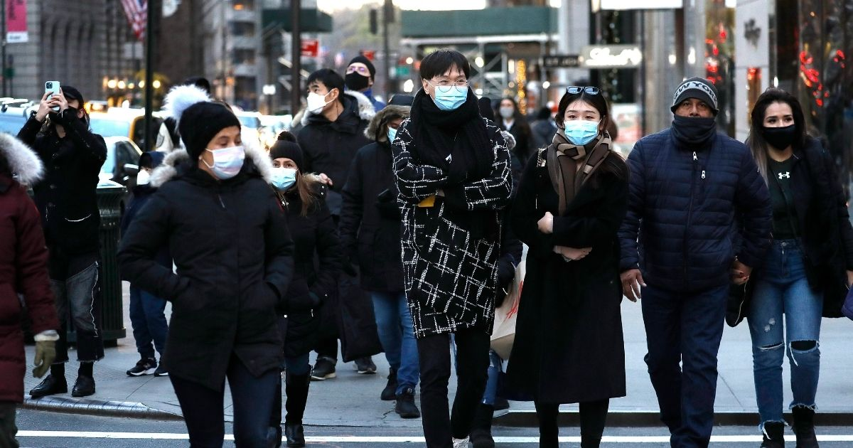 People wearing masks cross a street in New York City on Sunday.