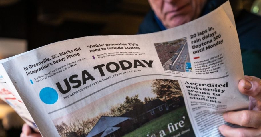 A man is pictured reading a USA Today newspaper in the stock image above.