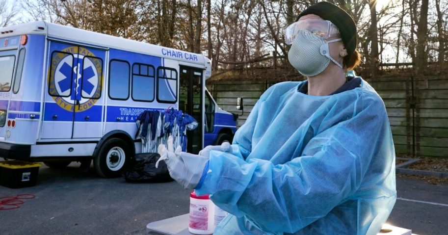 An emergency medical technician dons gloves to administer COVID-19 testing recently in Lawrence, Massachusetts.