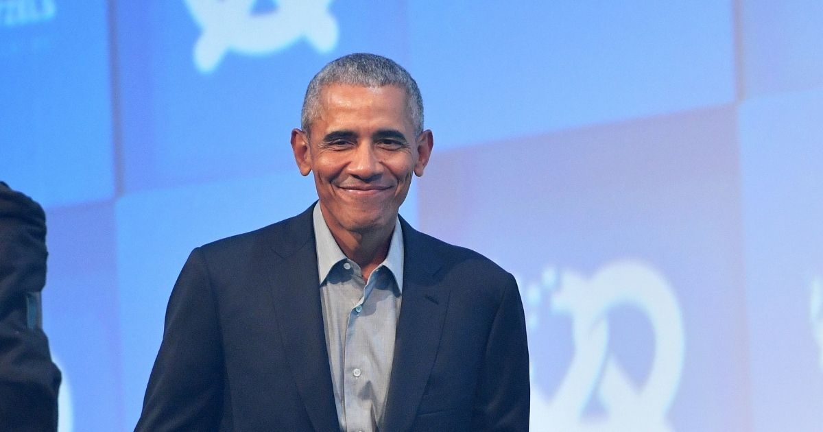 A grinning former President Barack Obama is pictured in a September2019 file photo from a technology expo in Munich, Germany.