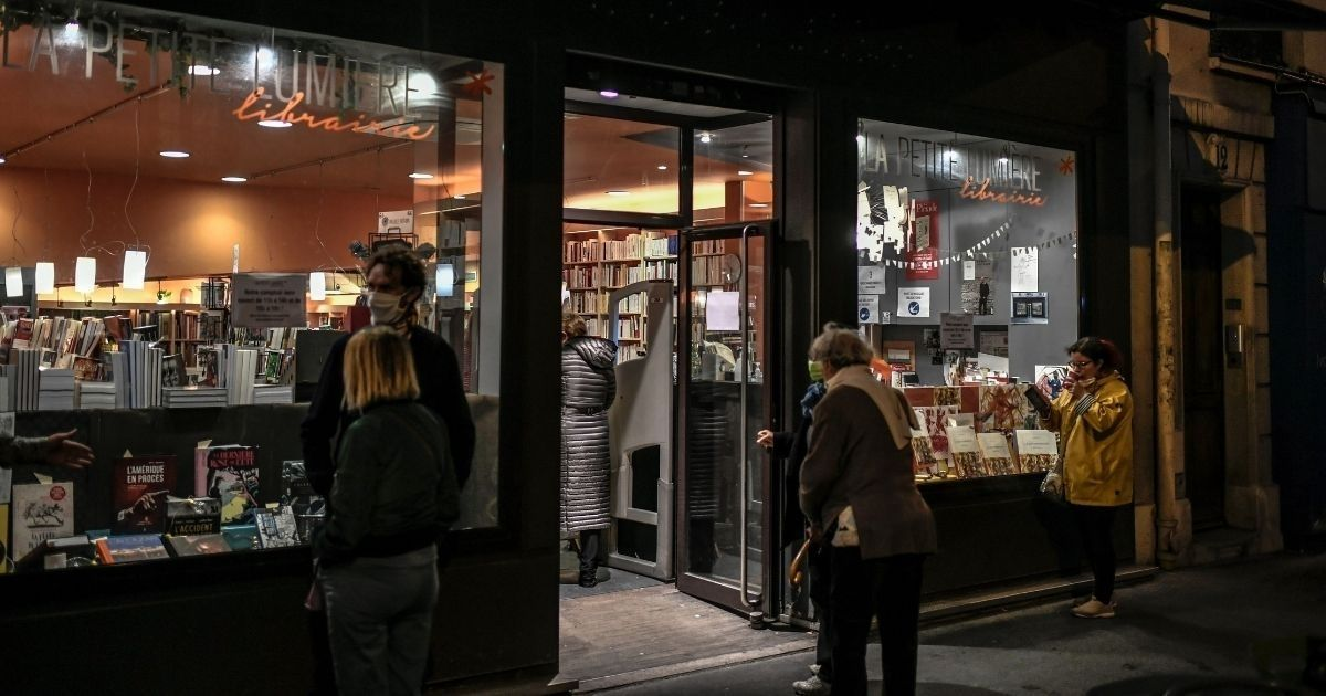 People wearing face masks gather outside a bookstore in Paris on Oct. 31, 2020. In Canada, a woman born without hands wasn't allowed in a Vancouver bookstore recently because she couldn't put on her mask.