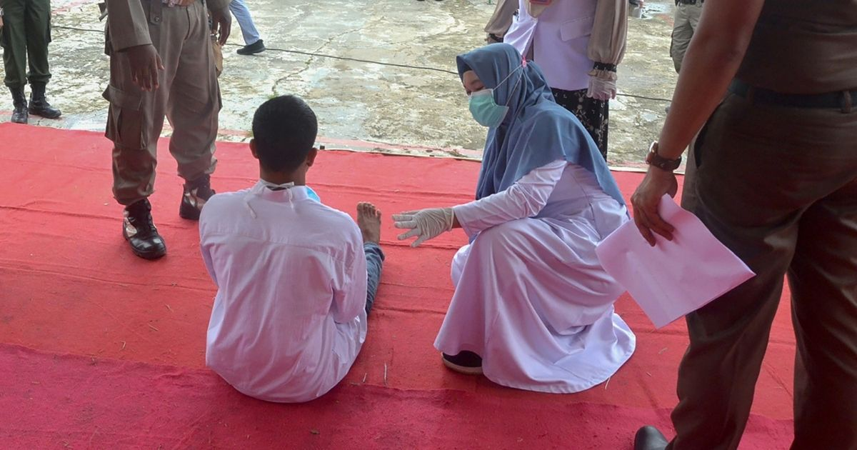 A man collapses in pain while getting publicly flogged by a member of the Sharia police after he was found guilty of raping a child, in Idi Rayeuk, East Aceh on November 26, 2020.