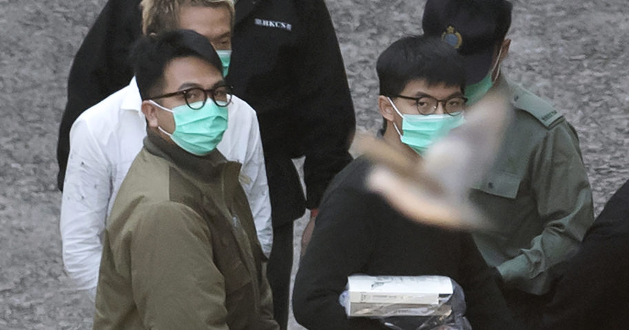 Pro-democracy activists Joshua Wong, right, and Ivan Lam are escorted into a prison van before appearing in a court in Hong Kong on Dec. 2, 2020.