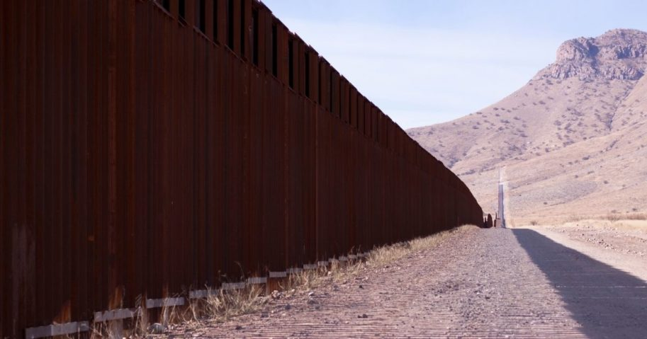 This stock image shows a fence in the desert.