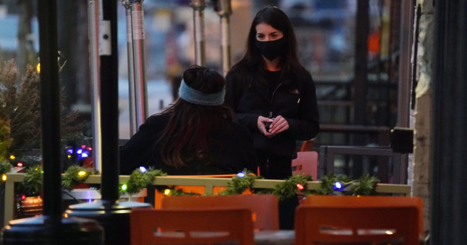 A waitperson wears a face mask while tending to a patron sitting in the outdoor patio of a sushi restaurant on Dec. 28, 2020, in downtown Denver.