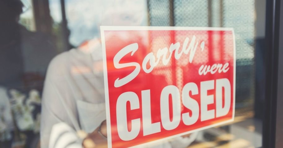 A woman posts a sign in a window in this stock image.