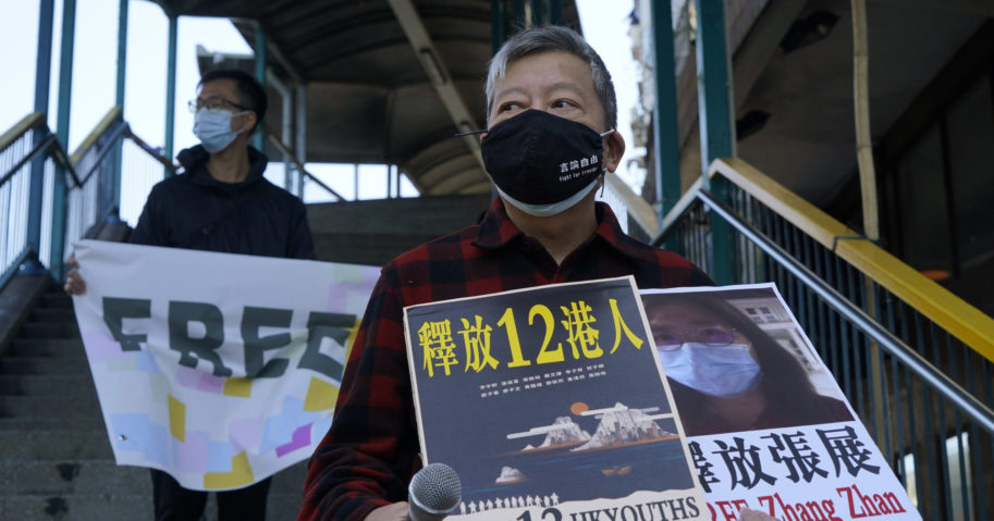 Pro-democracy activists hold placards as they march to the Chinese central government's liaison office in Hong Kong on Dec. 28, 2020.