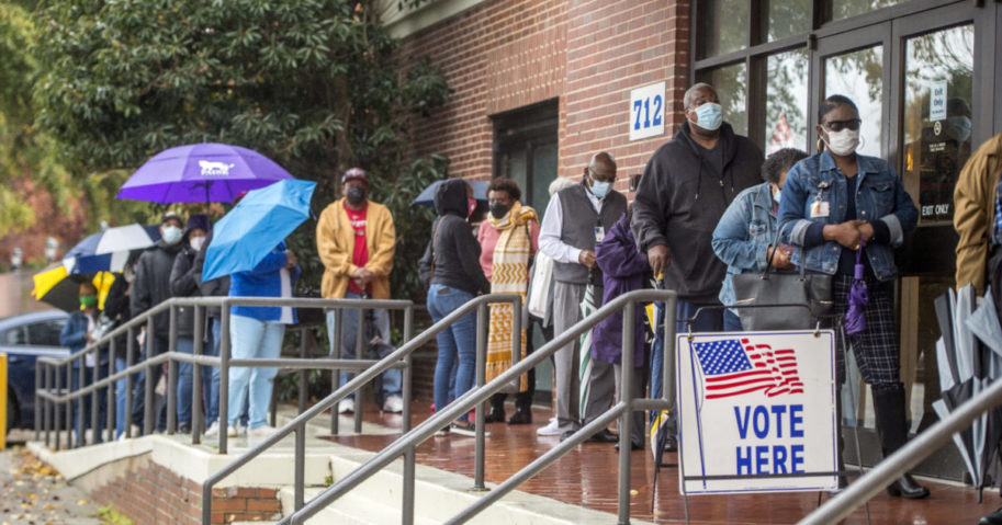 people wait in line on the first day of advance voting for Georgia's Senate runoff election