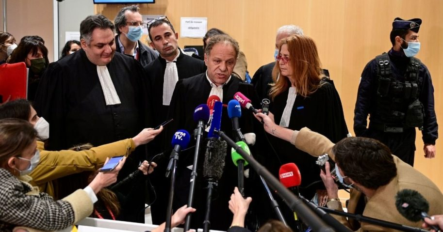 Lawyer Mehana Mouhou, center, talks to the media at a Paris courthouse on Dec. 16, 2020, after the sentencing hearing in the trial of 14 people suspected of acting as accomplices in the Charlie Hebdo jihadist killings.