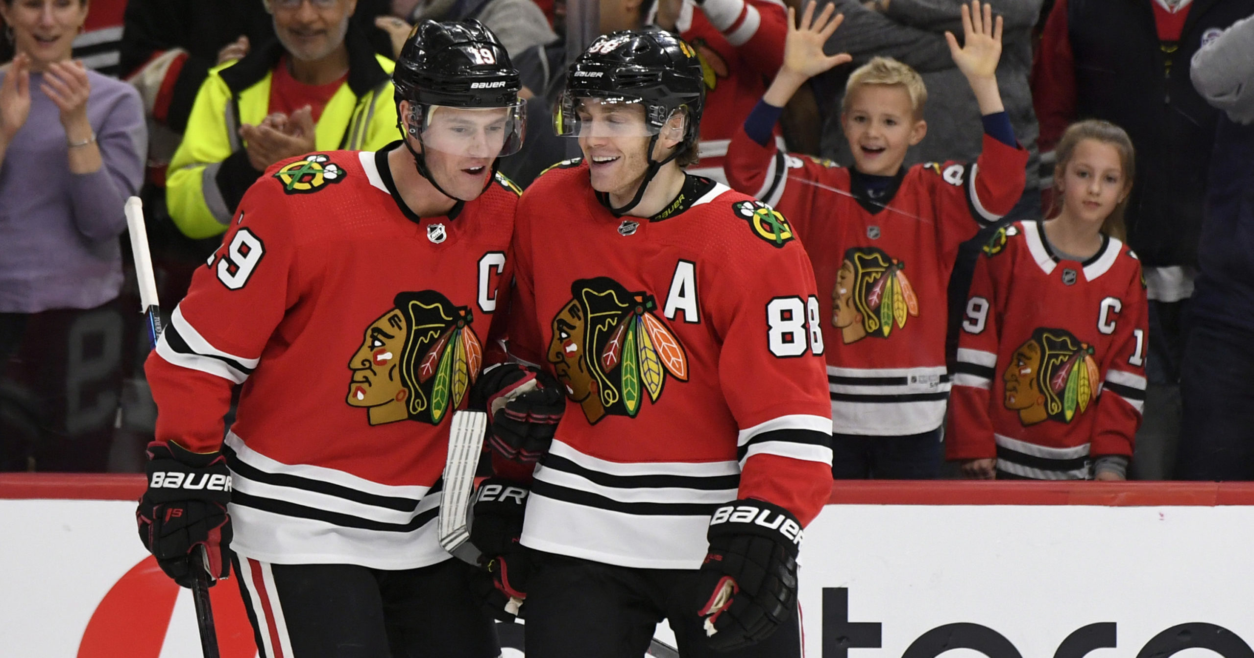 Chicago Blackhawks' Patrick Kane, right, celebrates with teammate Jonathan Toews after scoring a hat trick during the third period of an NHL hockey game against the Minnesota Wild in Chicago on Dec. 15, 2019.
