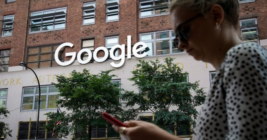 A woman looks at her smartphone as she walks past a Google building on June 3, 2019, in New York City.
