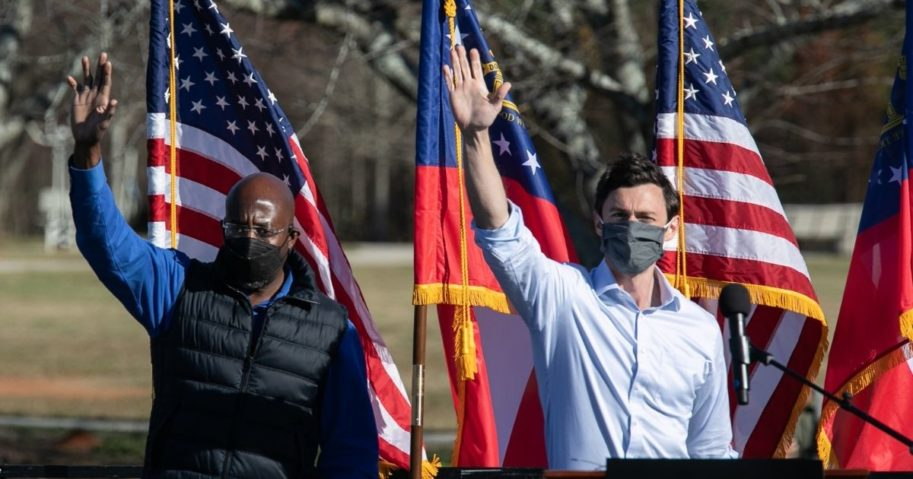 Democratic US Senate candidates Raphael Warnock, left, and Jon Ossoff wave to the crowd during a rally on Dec. 5, 2020, in Conyers, Georgia.