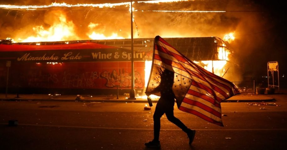 A protester carries a U.S. flag upside down, a sign of distress, next to a burning building May 28, 2020, in Minneapolis during protests over the death of George Floyd.