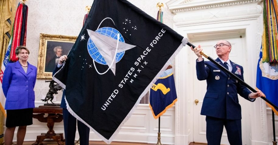Chief Master Sgt. Roger Towberman and Secretary of the Air Force Barbara Barrett present President Donald Trump with the official flag of the United States Space Force in the Oval Office of the White House in Washington, D.C., on May 15, 2020.