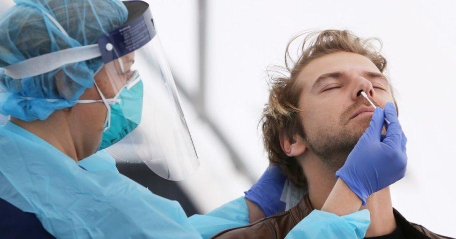 A nurse conducts a COVID-19 test on a man on July 22, 2020, in Sydney, Australia.