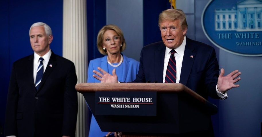 President Donald Trump speaks as Vice President Mike Pence and Secretary of Education Betsy DeVos look on during a briefing at the White House on March 27, 2020, in Washington, D.C.