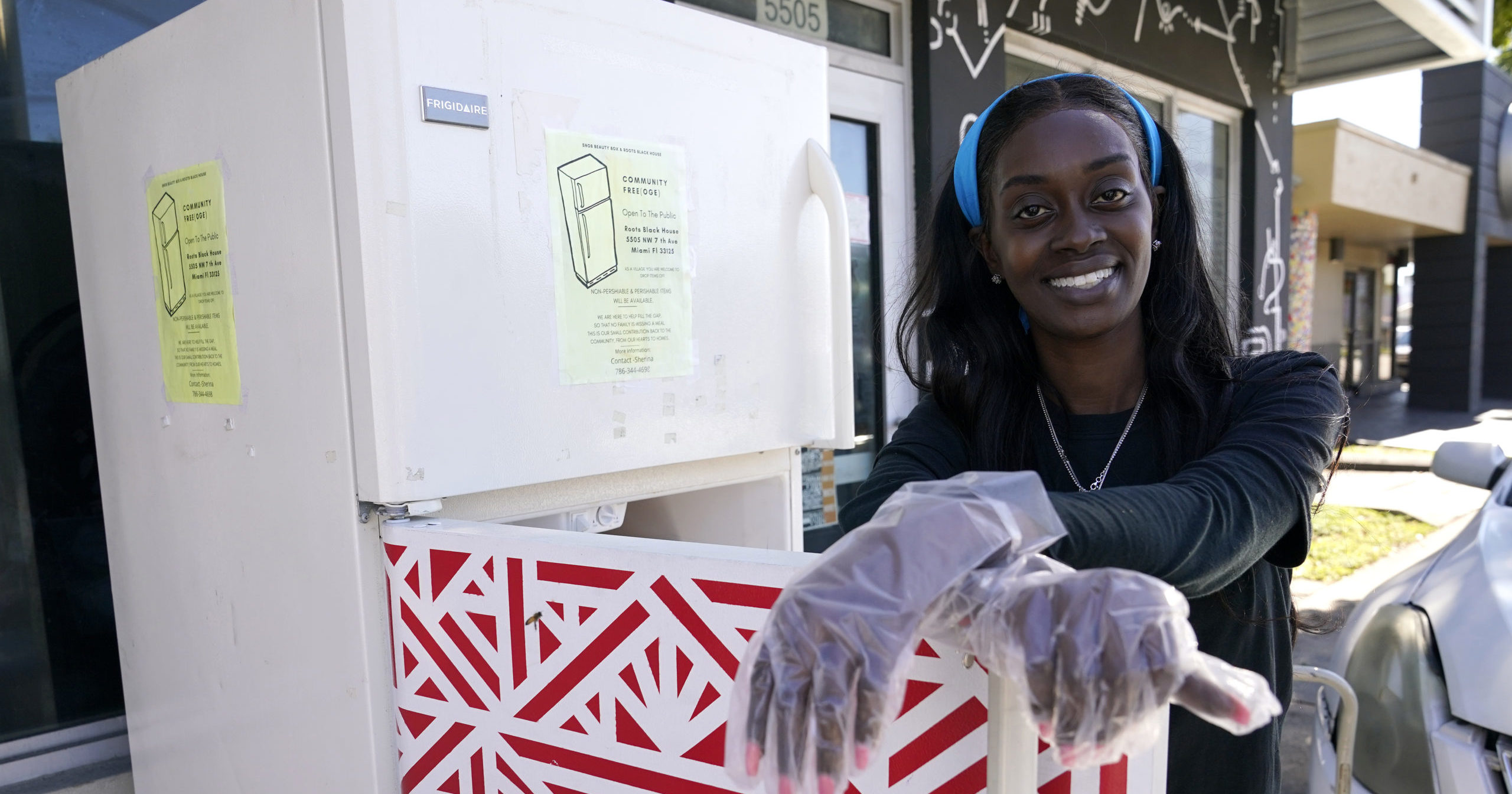 Sherina Jones poses with one of her community refrigerators on Dec. 9, 2020, in the Liberty City neighborhood of Miami.