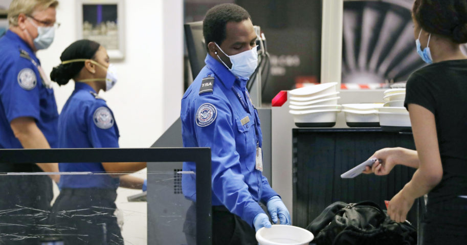 TSA officers wear protective masks at a security screening area at Seattle-Tacoma International Airport on May 18, 2020, in SeaTac, Washington.