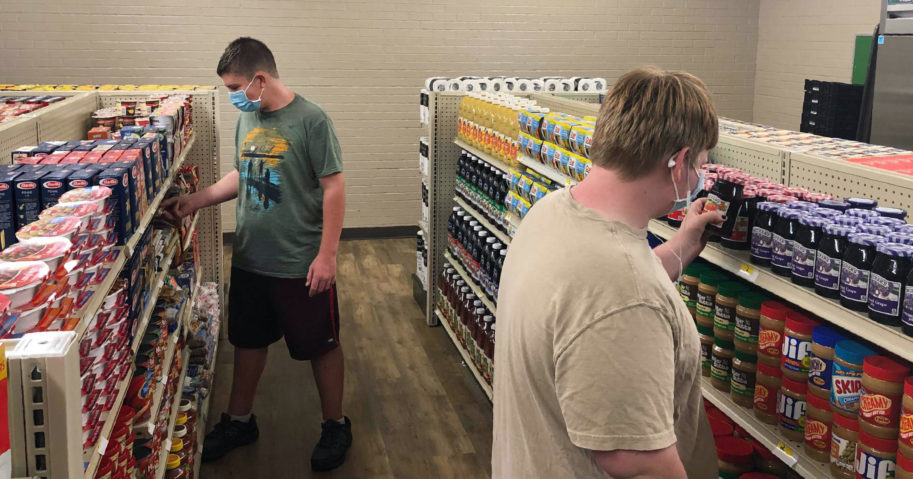 Student Hunter Weertman, 16, left, stocks shelves and takes inventory while working as a manager of the student-led free grocery store at Linda Tutt High School on Nov. 20, 2020, in Sanger, Texas.