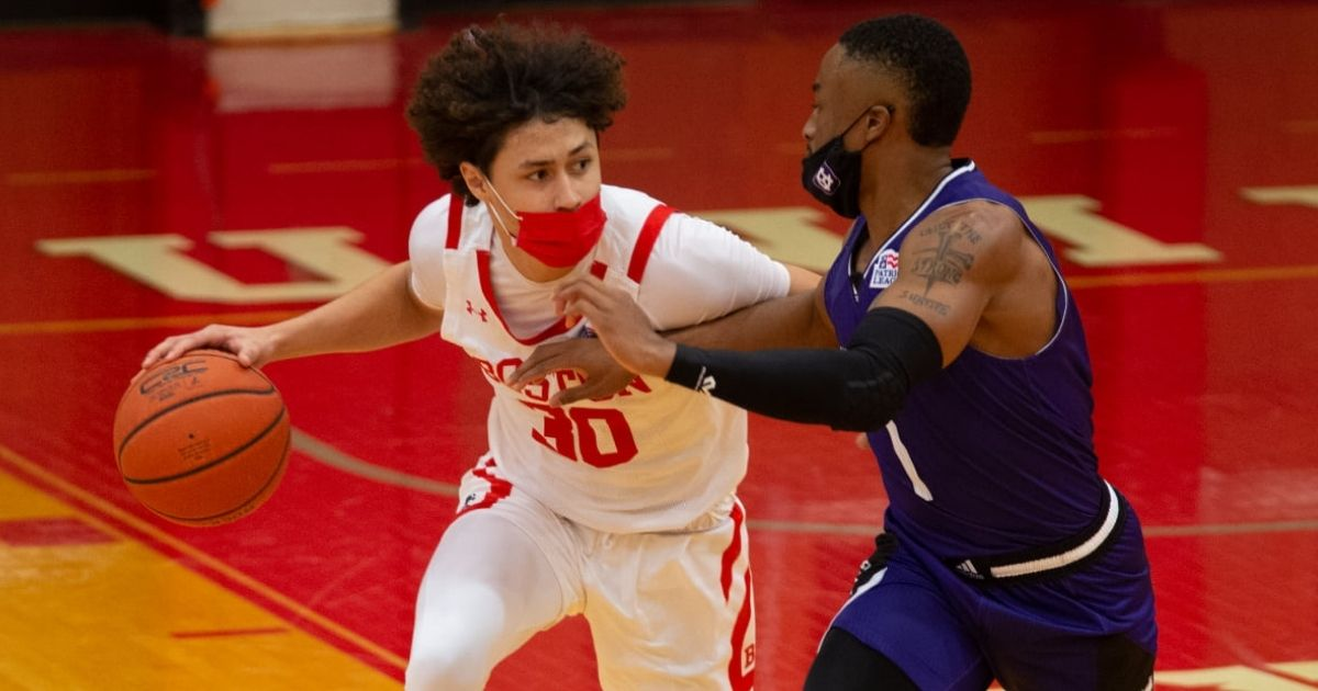 Boston University and Holy Cross players wear masks during their basketball game in Boston.