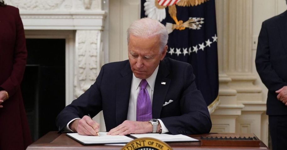 President Joe Biden signs executive orders as part of the Covid-19 response in the State Dining Room of the White House in Washington, D.C., on Thursday.
