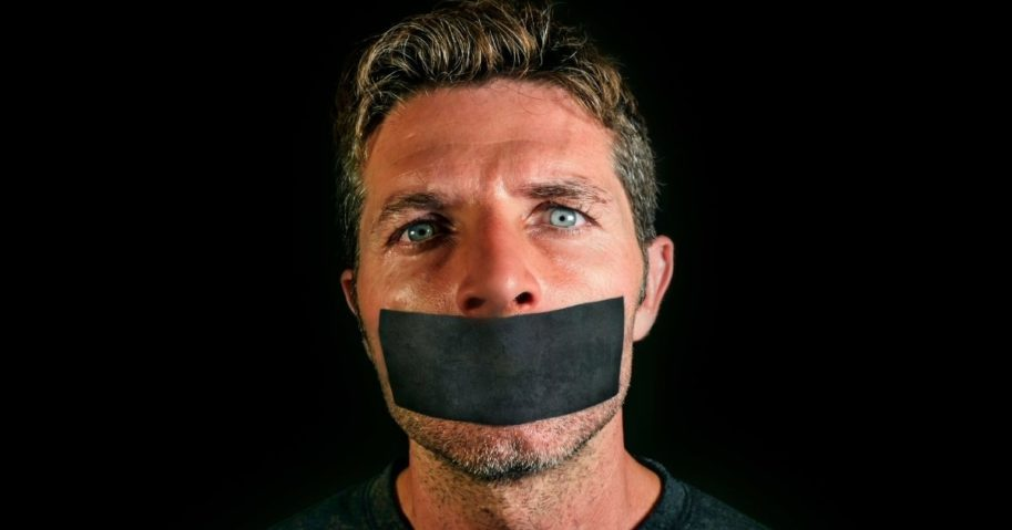 A man with tape over his mouth is pictured in the stock image above.