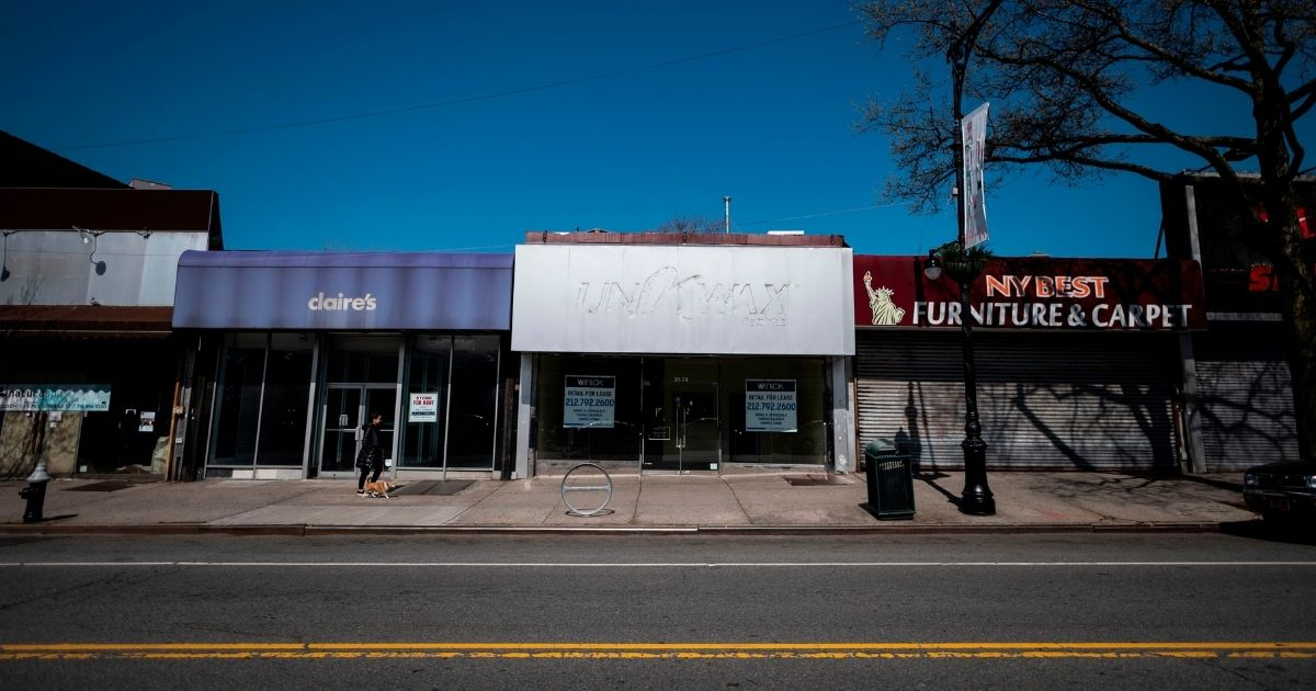 A woman walks past closed storefronts in the Astoria neighborhood of New York's Queens borough on April 15.