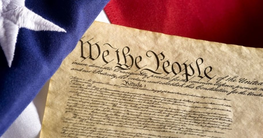 The U.S. Constitution is pictured with an American flag in the stock image above.