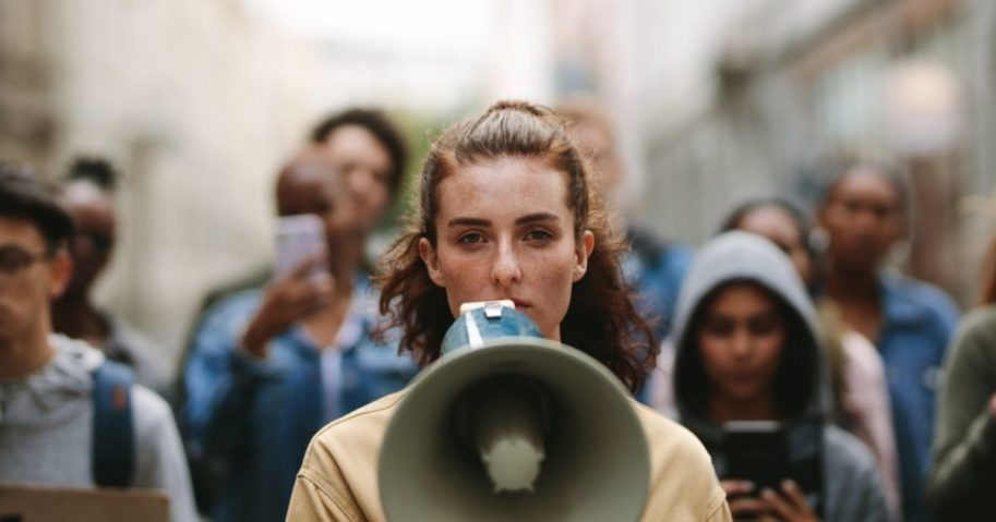 A group of demonstrators are led by a person with a megaphone in the stock image above.