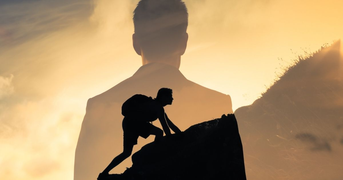 The above stock image shows a man climbing a steep mountainside.