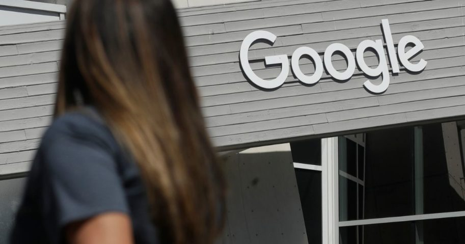 In this Sept. 24, 2019, photo a woman walks below a Google sign on the company's campus in Mountain View, California.