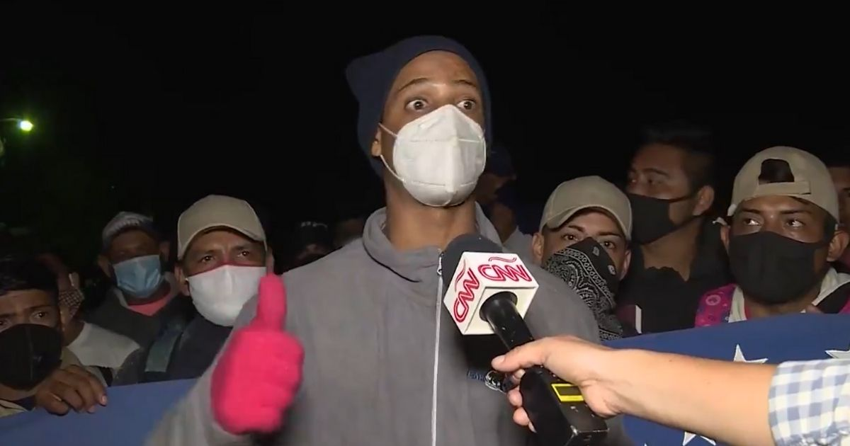A Honduran migrant talks to a CNN reporter.