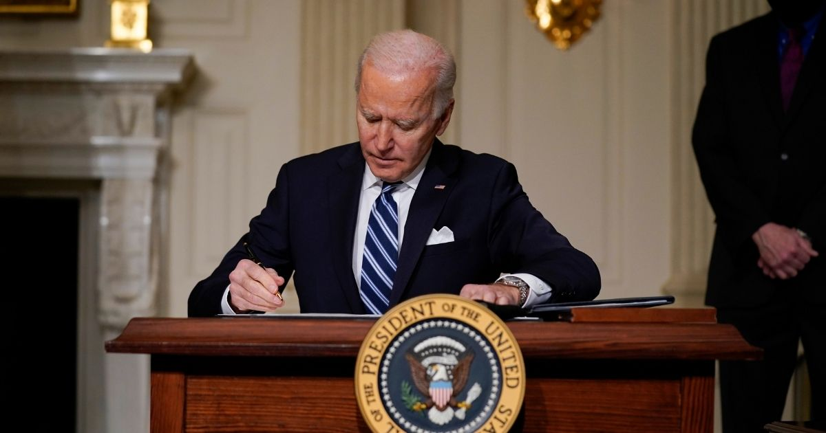 President Joe Biden signs an executive order on climate change in the State Dining Room of the White House on Wednesday in Washington.