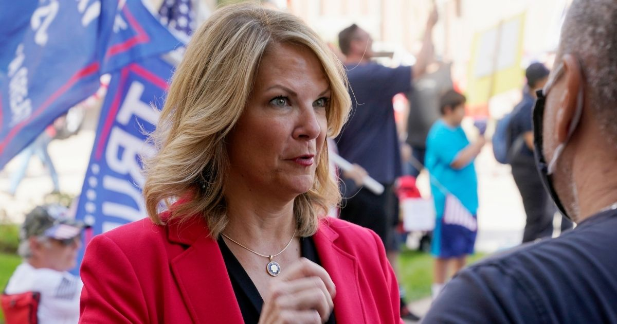 Dr. Kelli Ward, chairwoman of the Arizona Republican Party, talks with a supporter of then-President Donald Trump at a rally outside the Arizona state Capitol in Phoenix on Nov. 7.