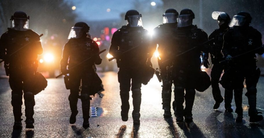 Police disperse demonstrators during a protest against COVID-19 restrictions in Salem, Oregon, on Friday.