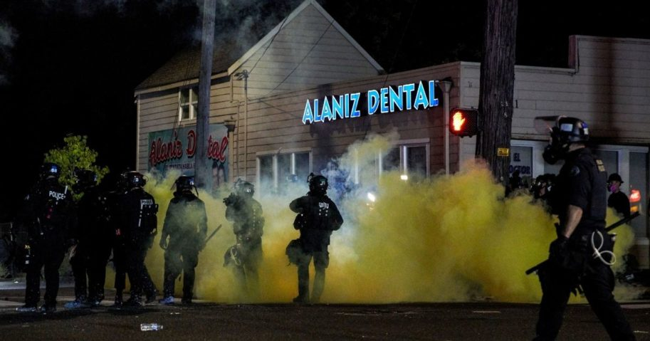 Oregon police wearing anti-riot gear march toward protesters through yellow smoke during the 100th day and night of protests in Portland, Oregon, on Sept. 5, 2020.